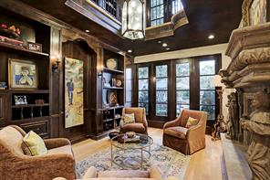 LIBRARY/STUDY is a two-story space with site-built Alder wood custom bookshelves with iron sconces, an imported iron & glass lantern chandelier, white oak flooring, recessed lighting, and an imported hand carved Cantera stone fireplace framed by statues of saints (that are removable if desired).