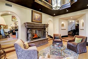 """Another view of the LIBRARY/STUDY showcases the extraordinary stone fireplace and arched entries into the adjacent FAMILY ROOM.  Notice the lighted arch niches on the right and the faux painted, """"leather-look"""" ceiling."""
