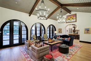 Another view of the FAMILY ROOM with gleaming hardwood floors and a large arched entry into the CHEF'S ISLAND KITCHEN to the right.