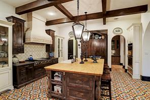 CHEF'S ISLAND KITCHEN has a pair of matching display armoires with German glass inserts.  Notice the Venetian plaster vent hood with imported tile accents, the expanse of exquisite imported tile flooring and the Italian tile backsplash over the cooktop.