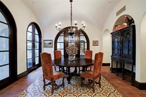 Spacious BREAKFAST ROOM with a groin vaulted ceiling, Spanish Cotto tile flooring with a custom encaustic tile center, arched mahogany doors leading to the pool and outdoor loggia, a sizable imported iron chandelier, and an arched art & furniture niche.
