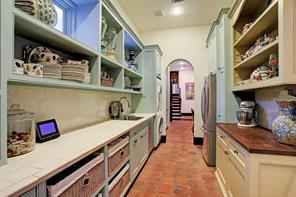 CATERING KITCHEN & STORAGE off of the Chef's Island Kitchen is perfect for large dry good & holiday china storage, and plenty of prep space for caterers.  Included are an extra refrigerator for large trays & beverages and a stackable washer & dryer to wash table linens.