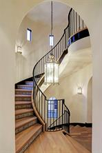 THREE-STORY CIRCULAR STAIRCASE has hardwood treads and encaustic tile risers.  Notice the custom lantern silver leaf chandelier and silver leaf sconces.  Also notice the handmade custom wrought iron railings.