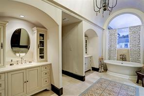 MASTER SPA BATH has polished stone floors with an imported encaustic tile center, both vanities have stone counters with under mounted sinks, and there is a custom made chandelier, a plastered barrel ceiling with cove lighting, a beverage station and a free-standing rolled edge tub.