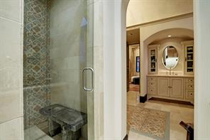 WALK-IN SHOWER with a seamless glass door has a stone bench, a tile surround including one wall with imported encaustic tiles and multiple shower heads.