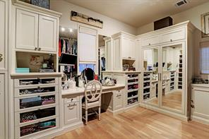 """There are HIS & HERS MASTER CLOSETS in the Master Suite - THIS IS """"HERS"""" and has extensive built-ins including a dressing table, mirrored front wardrobe, a furniture-style armoire and a jewelry closet.  Windows (with shades) offer ample natural light so you can make sure you're wearing navy instead of black!"""