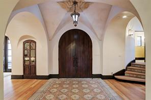 FOYER with groin vaulted Venetian plaster ceiling, imported 19th century antique European encaustic tile flooring, handmade imported chandelier and solid mahogany arched double front door.