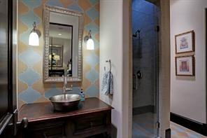 EN-SUITE BATHROOM with custom tile wall behind vanity with vessel sink and custom tile flooring.