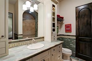 EN-SUITE BATHROOM with custom tiles throughout and excellent built-in storage.  The tile floor continues into the closet behind the rustic Alder door.  This bathroom has a tiled shower/tub with a barrel ceiling.