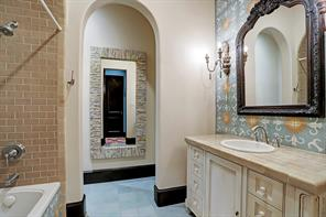 EN-SUITE BATHROOM has decorative tile floors, walls and shower surround.  There are custom encaustic tiles behind the vanity and on the front of the bathtub.  So beautiful!