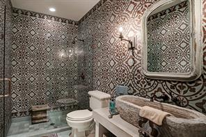 EN-SUITE BATHROOM in the Casita or Secondary Bedroom has extraordinary custom encaustic tiled walls and floors, a stone vessel sink from a flea market in Paris on a concrete base with shelving below and a large shower with a stone bench.