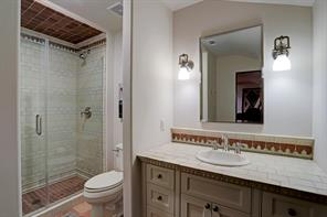 EN-SUITE BATHROOM with walk-in shower with seamless glass doors and a tiled surround, and a vanity with a tiled countertop and decorative tile backsplash.