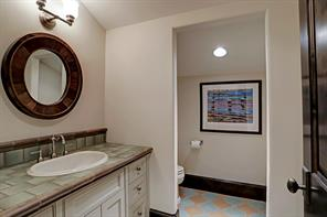 HALF BATH in Game Room, Wet Bar Area has decorative tile floors, and a vanity with a tiled countertop and backsplash.