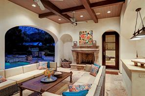 The LOGGIA WITH SUMMER KITCHEN overlooks the pool, spa and backyard, and has Cantera stone flooring, a wood clad ceiling with beams, two ceiling fans and a sizable wood-burning stone fireplace.