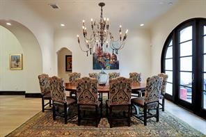 FORMAL DINING ROOM with imported chandelier, arched solid mahogany door & windows, rolled ceiling, and private courtyard through door to the right.  The Formal Dining Room is adjacent to the BUTLER'S PANTRY.  Please notice the detailed arched entry.