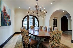 The FORMAL DINING ROOM, with hardwood floors and recessed lighting, is adjacent to the WINE ROOM.