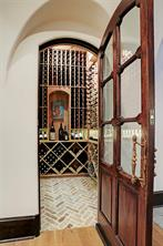 WINE ROOM with an eyebrow arch entry, a mahogany divided light door with two different door handles from a Paris flea market, Old Chicago brick flooring in a herringbone pattern, an art niche, and the capacity to store over 900 bottles of wine.
