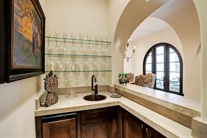 WET BAR across from the WINE ROOM has a barrel-vaulted ceiling, Old Chicago brick flooring, poured concrete countertops with aging finish, a copper sink, glass shelving for glassware, a refrigerator & ice maker.