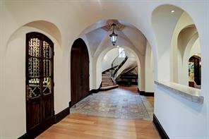 Looking back at FRONT ENTRY & FOYER with the WINE ROOM on the left and the WET BAR to the right.  Beyond is a staircase leading to the POWDER BATH and upstairs.