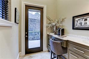 Hallway with built in desk has bright granite counter tops and directly leads to the backyard.