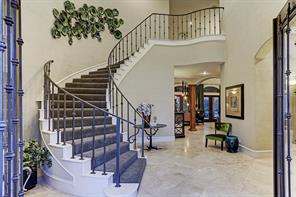 Upon entrance is the carpeted spiral staircase and a glimpse of extended living room area. Exquisite Traventine stone flooring from Brazil is found throughout the downstairs.