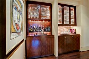 The well-positioned BAR AREA is located at the end corner of the Front Entry and the opening to the Kitchen.  The area is two fold with a Hall Bar and an Interior Bar.  The Hall Bar is shown here with its built-in wood cabinets and glass front cabinets above with beveled glass fronts/interior lighting, under cabinet lighting, onyx countertops.