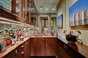 The interior Bar is shown here with onyx countertops/backsplash, aged copper sink with ornate fixtures, Dauphin antiqued mirrored walls, beveled glass front cabinets with interior lighting, under cabinet lighting, Sub Zero ice-maker.