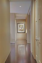 Shown here is the Hallway from the Bedroom wing of the residence, past the Front Entry Hallway and leading to the Bar area and Kitchen beyond.  Notice the gleam of the Ipe Brazilian walnut flooring from the recessed lighting and the sophisticated hardware used on interior storage closets.