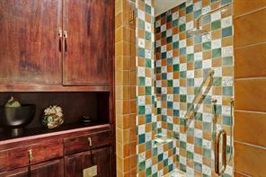 Further detailing of the GUEST BATHROOM showing the custom designed built-in cabinetry with antique Asian hardware and the glass front walk-in shower with the Paris Ceramics'  Papal tile surround shower/built-in bench/Dornbracht plumbing  fixtures.