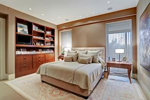 Also notable in the MASTER BEDROOM SUITE is the handsome wall of built-in cherrywood shelving with magazine rack and storage cabinets below.