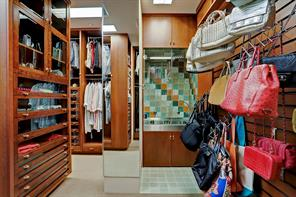 Another view of CLOSET #1 with its Roma steamer system (glass enclosure/stainless sink).  Also notice the room's varying storage spaces for clothing accessories. There are also a number of telescopic clothing rods in closet cabinetry that can be extended for additional hanging.