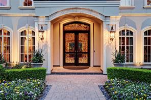 A close up image of 70 Williamsburg Lane with double Canterra-style doors, lovely arched windows in the Study (right of the image) and Dining Room (left of the image).  Custom built in 2004/HCAD by Jonathan Casada.  Professionally landscaped front and back yards and lighting 2018 by Houston Lightscapes.