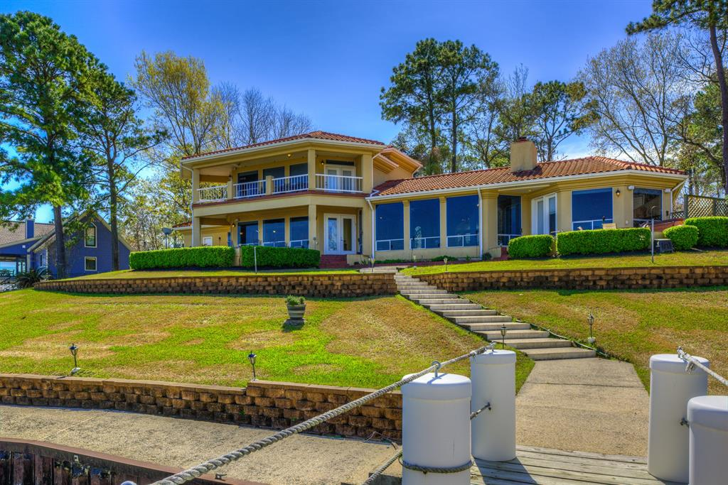 Beautifully situated on two lots overlooking Lake Livingston, this Mediterranean 1.5 story home has a view from every room in the house. From the moment you enter the large great room with fireplace and wet bar, the picture windows across the lakefront, upstairs and down, capture the waterfront scene with Pine Island in the distance. The kitchen is open to the dining area and family room. Wood beamed ceilings throughout enhance the picture. The master suite with large bath and walk-in closets is positioned on the end for privacy. Upstairs are two en-suite guestrooms with balcony. There are multiple spaces for outdoor living including a large partially covered patio with firepit, gracefully tiered lawn, and the spacious dock around the boathouse. This is a one of a kind home on Lake Livingston!