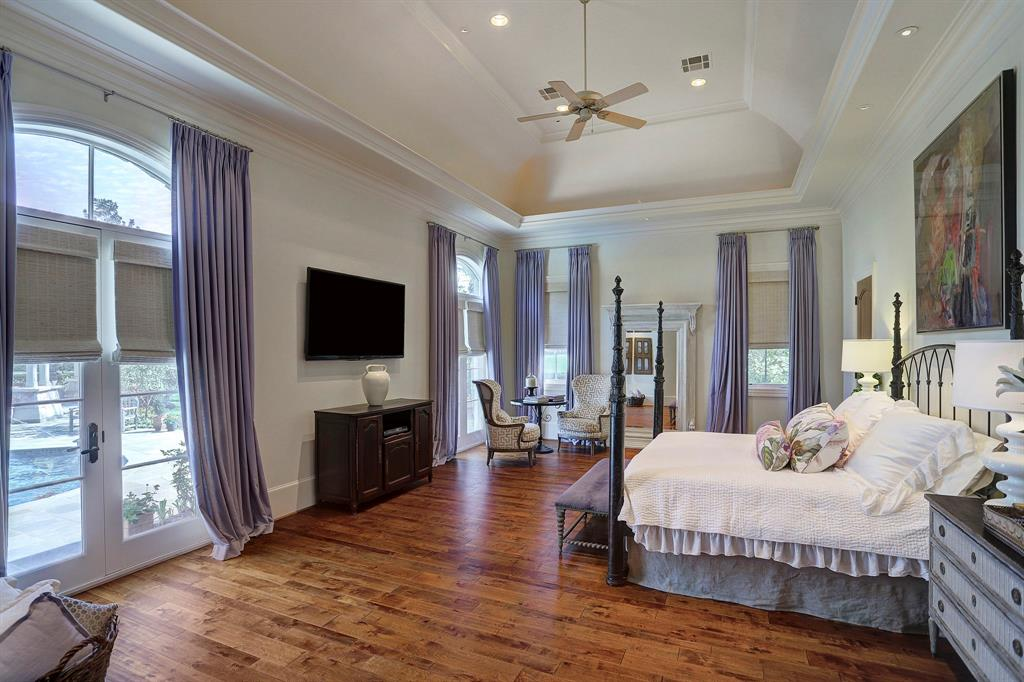 The first floor master bedroom with vaulted ceiling and wood floors, overlooks the pool and side yard.