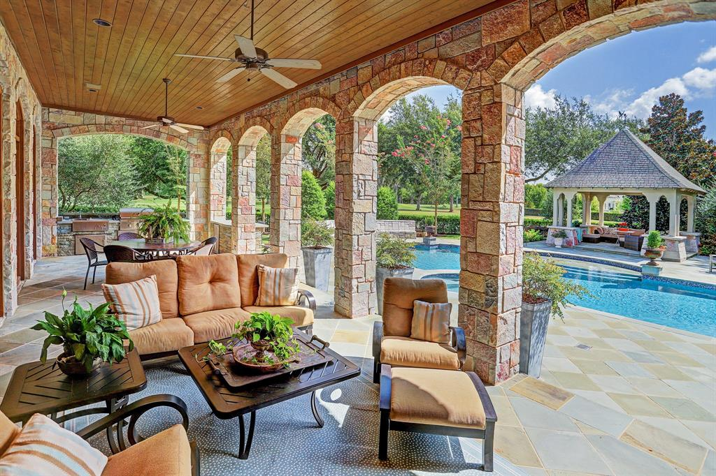 The backyard is anchored by an oversized pool, spa, and covered seating area.