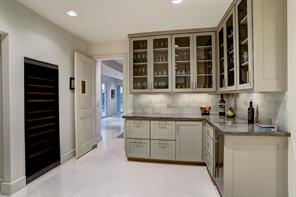 The open BAR / BUTLER'S PANTRY features a full size wine chiller, ice maker and deep drawers.  Upper glass-front cabinets have great space to display crystal and barware.
