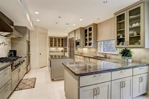 The fantastic KITCHEN (17'x13') was redone in 2012-2013.  It features beautiful stone countertops and subway tile in neutral colors, slab limestone floors and baseboards and plenty of lower and upper cabinets with under-cabinet lighting.