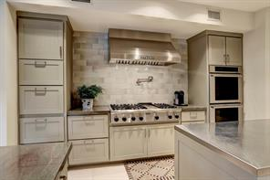 Fantastic cooking space with Thermador package with 6-burner gas range with griddle, vent hood and double ovens.  Other features include a pot filler and side-tiered spice racks inside the deep drawers.  The stainless-top island offers a great prep surface.
