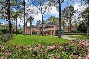 Timeless Cedar Bayou brick exterior with extensive verandas that overlook the amazing grounds, pool and freestanding pavilion with summer kitchen.