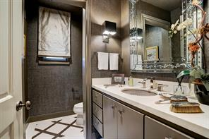 The FRONT POWDER ROOM is conveniently located out of the way and features elegant fabric wall & ceiling coverings and limestone counters.