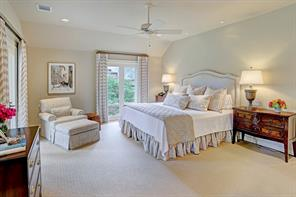 Elegant MASTER BEDROOM (17'x14') with hardwood floors covered by a custom rug, windows on two walls that fill the room with light. It has raised ceilings with recessed and reading lights and a ceiling fan.