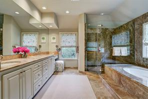 MASTER BATHROOM with double sinks and vanity area, Kohler tub and spacious walk-in shower with slab walls and seamless glass enclosure, two fixed shower heads and corner seat.
