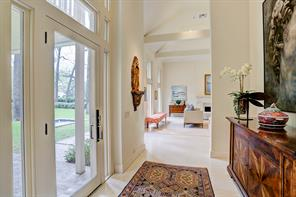 Elegant double height Entry with glass door and side lights with transoms.  The windows above extend to the ceilings filling the entrance with natural light.  The beautiful cut-to-size slab limestone floors are found throughout the first floor.
