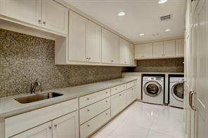 Wonderful UTILITY ROOM (18'x8') with extensive Silestone quartz counters, sink, wall to wall upper and lower cabinets and two storage closets.