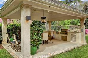 The OUTDOOR PAVILION & SUMMER KITCHEN is the perfect place to enjoy the outdoors all year long!  There is plenty of room for a dining set as well as a side sitting area while two ceiling fans help keep the area cool.