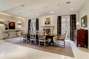 The expansive FORMAL DINING ROOM (23'x14'), with a limestone gas log fireplace flanked by windows overlooking the private courtyard, is ideal for large gatherings as well as more intimate dinners.