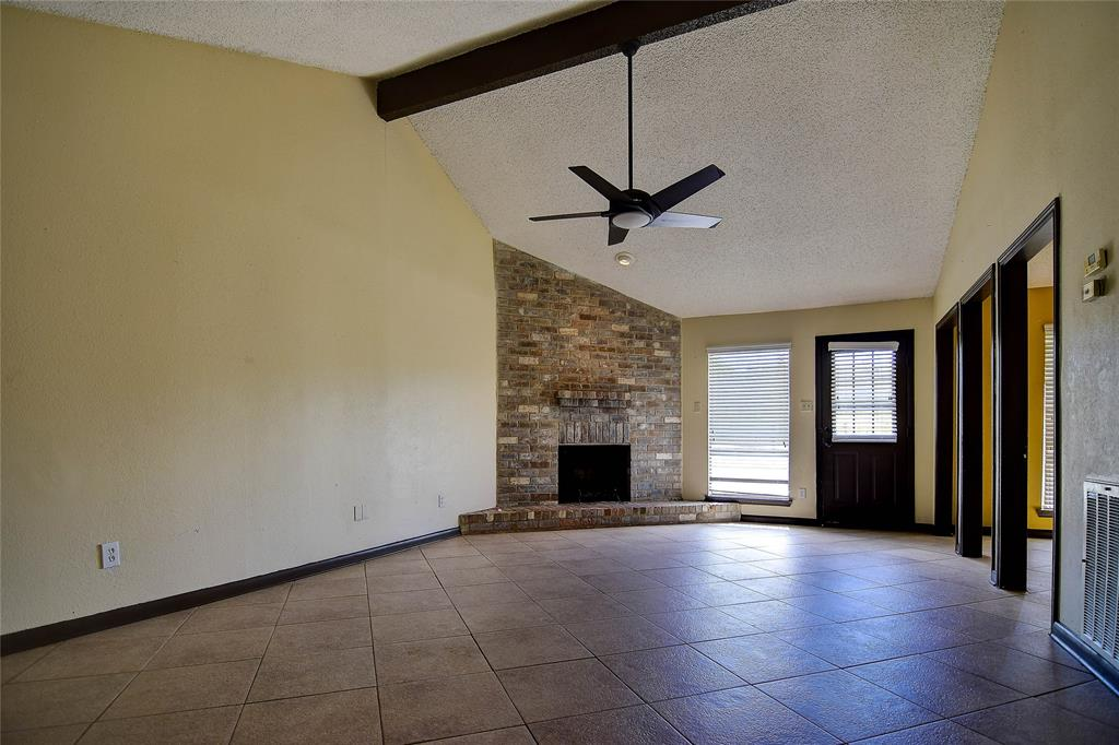 Upon Entering You Are Greeted By A Spacious Family Room That Features Tile Flooring Vaulted Ceiling And Brick Fronted Corner Fireplace