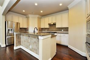 Granite Island Chefs Kitchen with Upgraded Cooktop, Stainless Appliances and Tumble Tile Backsplash and Island Accent.