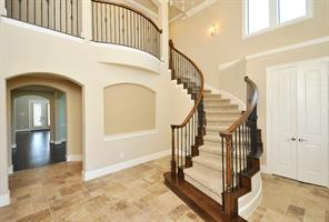 Two Story Entry with Travertine Flooring an a Sweeping Wrought Iron Stairway