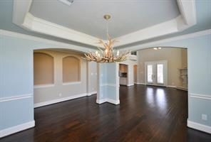 Beautiful Wood Floors in the Dining Room with lots of Crown Molding and Coffered Ceiling